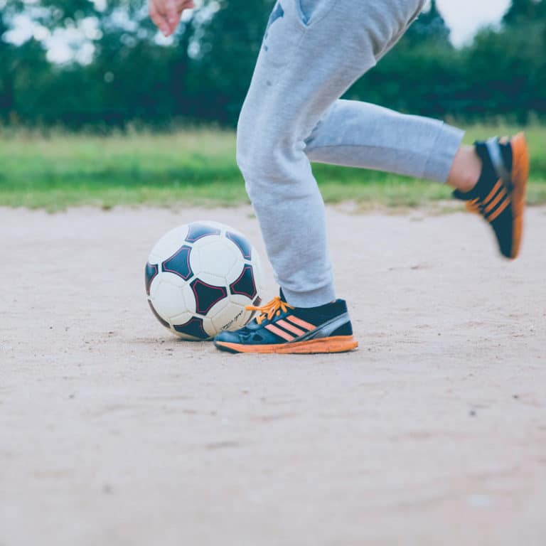 healthy child playing soccer after pediatric chiropractic adjustment